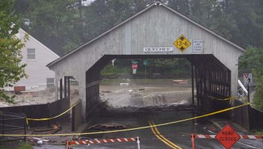 Closed covered bridge in front of flood waters from Tropical Storm Irene in Quechee, Vermont