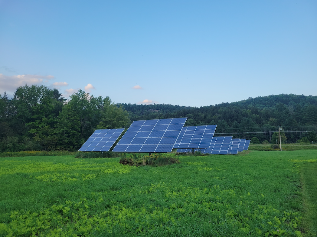 Solar panels on green field with blue sky